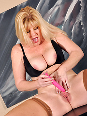Busty blonde cougar shoves a toy into her creamy pussy